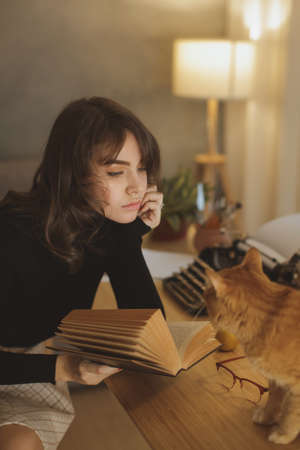 Young beautiful woman relaxing at home with cat in the cozy evening and reading book. Relaxed holiday evening concept. Fine art photo of a calm woman resting indoors 写真素材