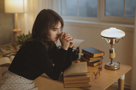 Young beautiful woman relaxing at home in the cozy evening and reading book. Relaxed holiday evening concept.