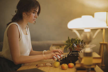 Young woman typing on a typewriter. Fine art photo of a calm thinking writer woman working at the desk.