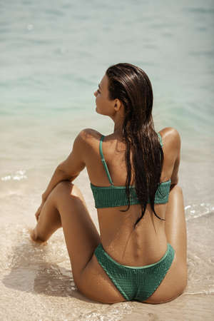 Woman in swimsuit sitting on the beach and looking at the sea. Back view of a stunning girl resting during summer vacation