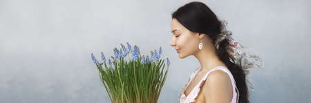 Beautiful young woman smelling bouquet of spring flowers with closed eyes. Sensual romantic mixed race female florist with mouse Hyacinth Muscari in hands. Life lover, zero waste, spring mood concept.
