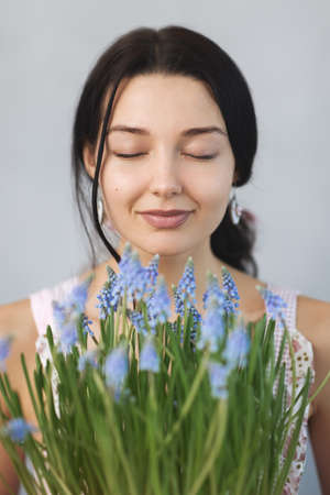 Beautiful young woman smelling spring flowers with closed eyes. Sensual romantic mixed race female florist with mouse Hyacinth Muscari in hands. Reklamní fotografie