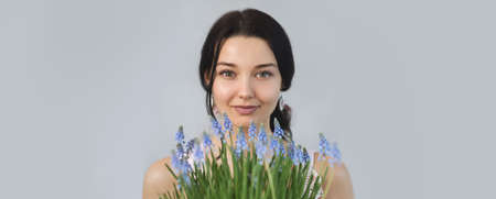 Beautiful young woman holding spring flowers bouquet in hands. Sensual romantic mixed race female florist with mouse Hyacinth Muscari. Life lover, zero waste, spring mood concept. Reklamní fotografie