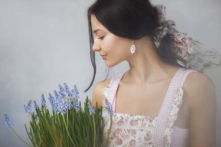 Beautiful young woman holding bouquet of spring flowers. Sensual romantic mixed race female florist with mouse Hyacinth Muscari in hands. Romantic close-up portrait Reklamní fotografie