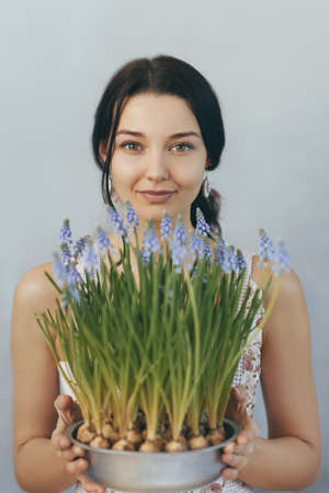Beautiful young woman holding spring flowers in flowerpot looking at the camera. Sensual romantic mixed race female florist with mouse Hyacinth Muscari in hands. Romantic close-up portrait Foto de archivo