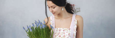 Beautiful young woman holding bouquet of spring flowers. Sensual romantic mixed race female florist with mouse Hyacinth Muscari in hands. Romantic close-up portrait Foto de archivo