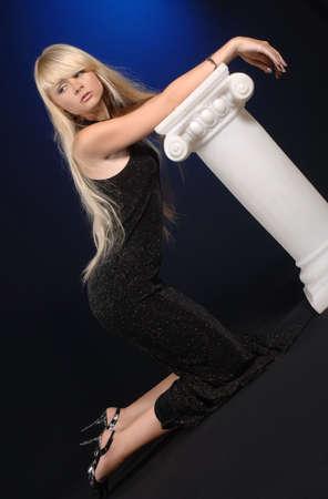 donna in ginocchio: giovane donna inginocchiata accanto alla colonna