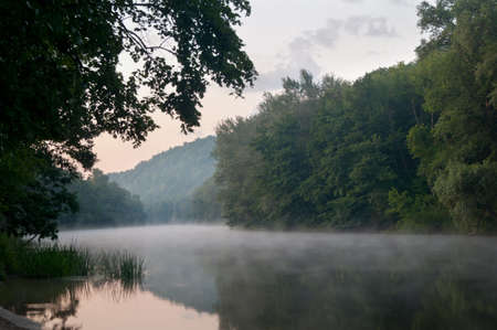 Sunrise and fog on the river photo