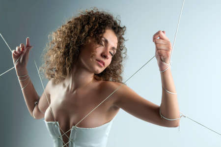Photo of girl in white dress with her hands tied with rope photo