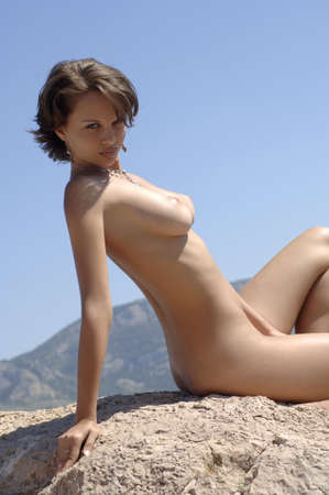 wet breast: woman lying on a rock  Stock Photo