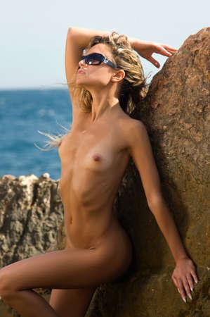 nue plage: femme debout sur un rocher près de la falaise  Banque d'images