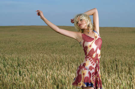 attractive young blonde woman standing in a wheat field on a warm summer day photo