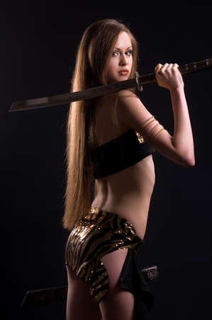 sword fighting: A beautiful woman with a sword in the studio on a black background