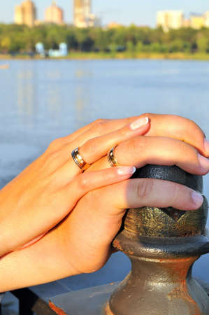 reciprocity: hands of newlyweds with wedding rings lying on the rails