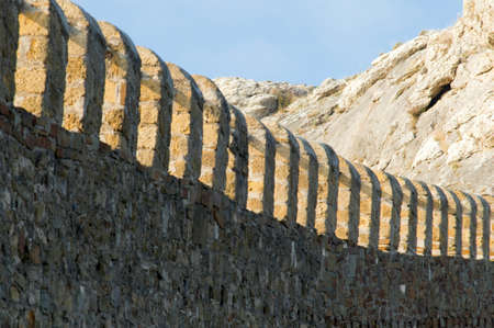 fortified wall: fortified wall of an ancient castle and the mountains Stock Photo