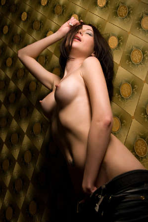 beautiful naked brunette close to the wall Archivio Fotografico