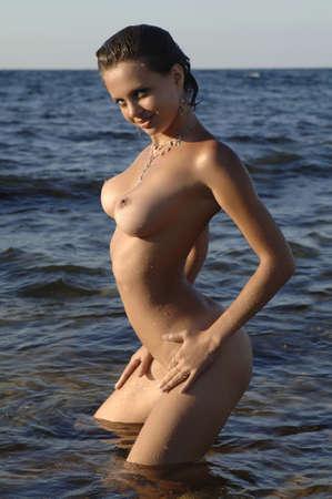 desnuda: mujer desnuda con una figura delgada de pie en el mar