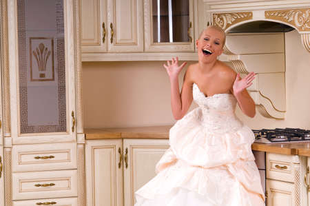 respectability: the bride laughs while standing in the kitchen