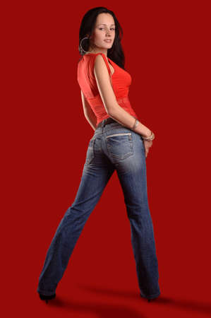 A young woman in jeans and a blouse on a red background