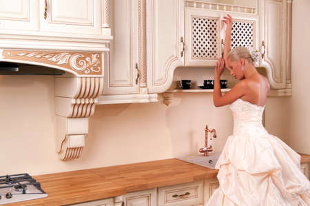 respectability: Bride in a luxury dress stands in the kitchen