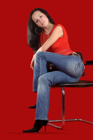 arm chair: young woman sitting on a chair with a red background