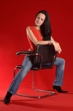 young woman sitting on a chair with a red background photo