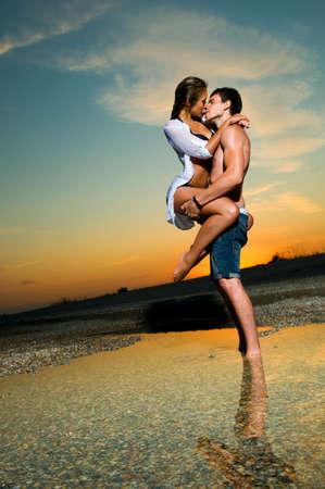 Joven pareja besándose en la playa con la configuración de sol detrás de ellos Foto de archivo - 9958951