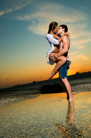 novios besandose: joven pareja bes�ndose en la playa con la configuraci�n de sol detr�s de ellos