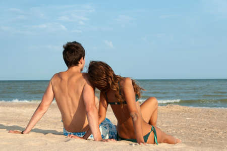 guy and his girlfriend sitting on the beach Stock Photo