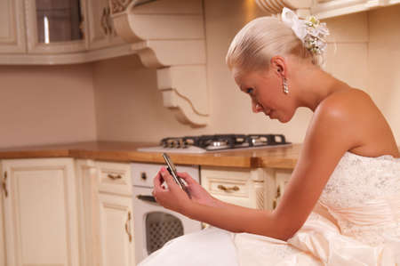 beautiful bride in the kitchen and laughs Stock Photo