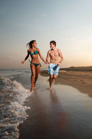 young boy and girl running on beach