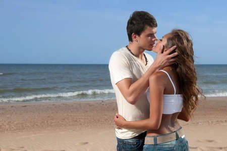 loving guy and a girl standing on the beach