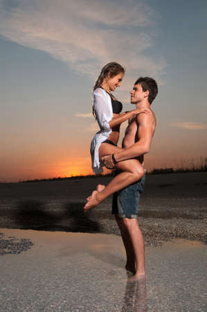 the guy is holding his girlfriend at sea