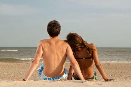 pareja apasionada: chico y su novia sentado en la playa