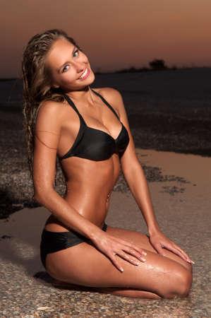 actitud positiva: Joven mujer sentada en posici�n de loto en una playa