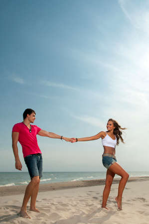 loving guy and a girl standing on the beach photo