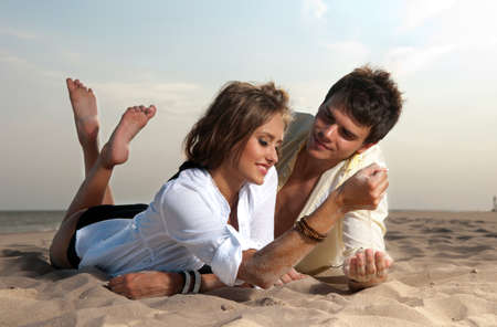 guy and his girlfriend are on the beach Stock Photo