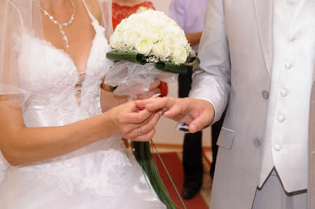 Bride putting a ring on grooms finger during wedding ceremony photo