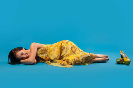 young woman in yellow lying on studio floor on blue background Stock Photo - 10952099