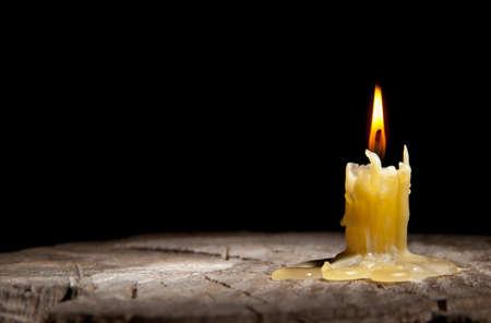 candle: oude kaars staat op de stronk van een boom op de zwarte achtergrond Stockfoto