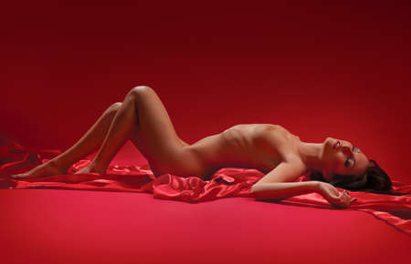 sensual naked brunette woman lying on a red background Stock Photo