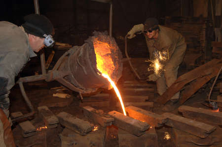 foundry: pouring molten metal from a ladle in a foundry