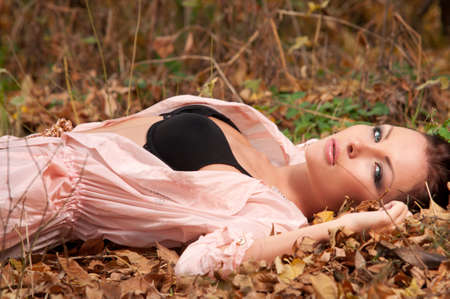 woman in elegant clothes lying on the leaves Stock Photo - 11144274