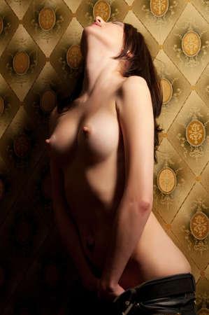 mujer desnuda senos: una atractiva mujer desnuda sentada en el sof�