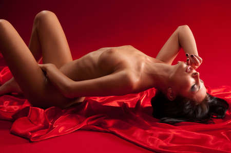 wet breast: Young naked brunette lying on the bed