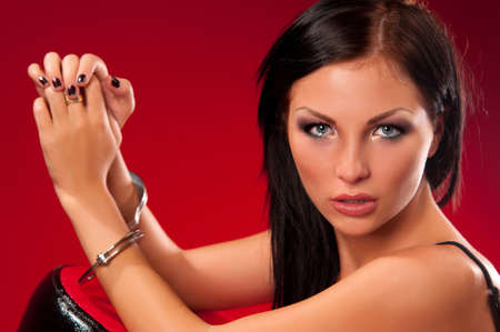 Beautiful brunette woman in handcuffs on a red background photo