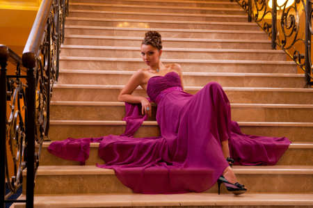 young woman in a long dress lying on the stairs in the hotel lobby Stock Photo - 11353715