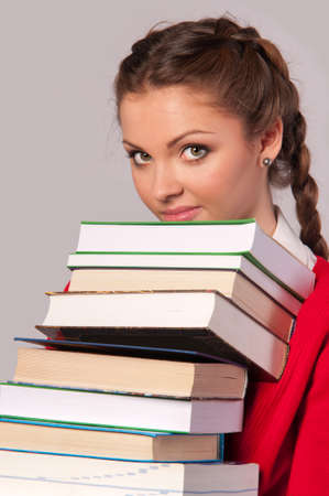 beautiful girl sitting in front of books,gray background photo