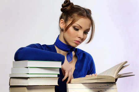 Young beautiful girl is sitting at the desk and reading the book Stock Photo - 11535936