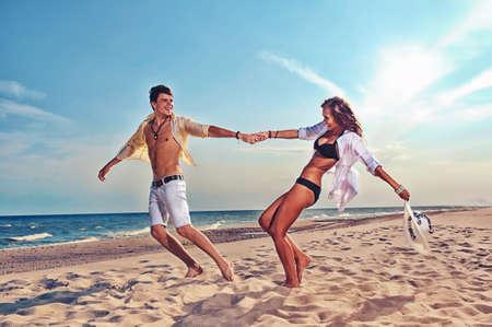 parejas felices: ni�o y ni�a corriendo en la playa Foto de archivo